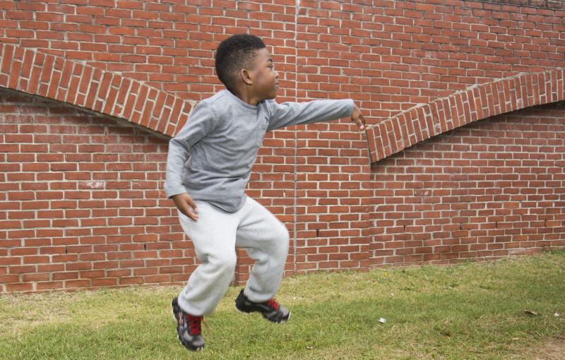 Boy jumping with a brick background